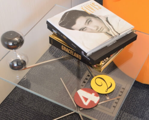 Sidetable with Elvis books and coasters that have the number 42