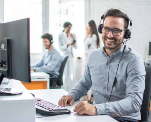 friendly guy wearing headset at computer